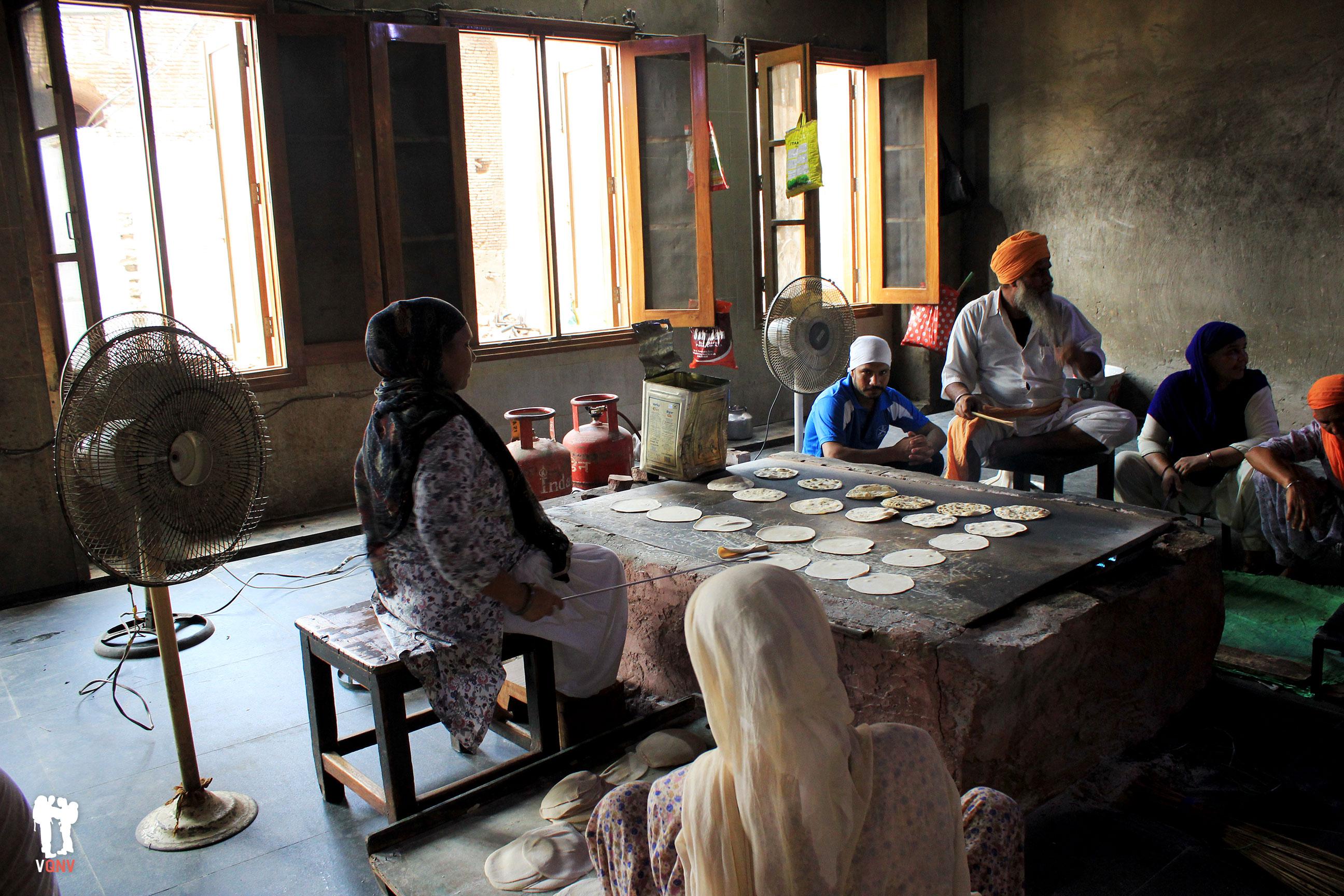 Voluntarios al lado del fuego preparando los chapatis